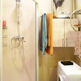 На фото: санузел с душевой кабиной, водогреем, настенным шкафчиком, стиральной машиной с фронтальной загрузкой, стены - плитка