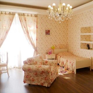 На фото: часть комнаты, одно окно, кровать у стены справа от окна, у кровати тумбочка, мягкое кресло, полы - ламинат, на потолке - люстра.