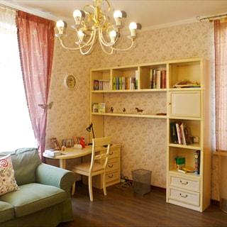 На фото: часть комнаты, два окна, письменный стол со стулом, книжные полки, мякгий диван, полы - ламинат, на потолке - люстра.