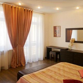 На фото: часть комнаты, окно, балконная дверь, двуспальная кровать, комод, туалетный столик, зеркало, полы - ламинат, на потолке - точечные встроенные светильники.