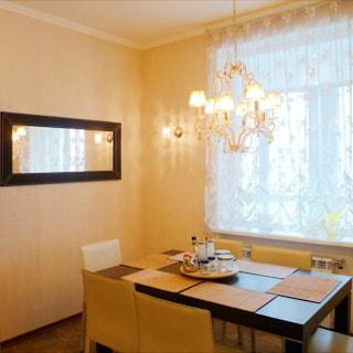 На фото: часть комнаты, окно, обеденный стол со стульями у окна, на стене - зеркало, полы - плитка, на потолке - люстра.