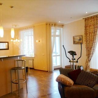На фото: часть комнаты, два окна, балконная дверь, барная стойка со стулом, спортивный тренажер, мягкое кресло, полы - плитка, на потолке - люстра, встроенные точечные и подвесные светильники.