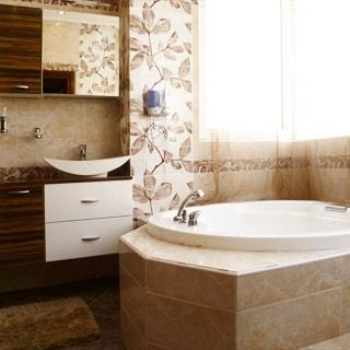 На фото: часть помещения санузла с ванной, окно, перед окном - ванная со смесителем, слева - раковина со смесителем на тумбе, навесной шкафчик с зеркалом, полы и стены - плитка.