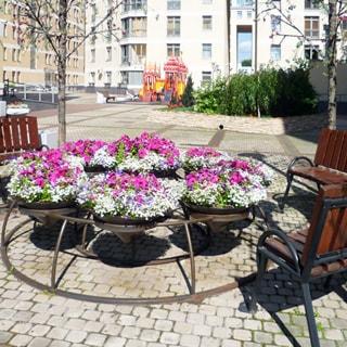 На фото: часть территории благоустроенного двора, цветочные клумбы на подставках, декоративные деревья, садовые скамейки, территория вымощена тротуарной плиткой, на дальнем плане - обустроенная детская площадка.