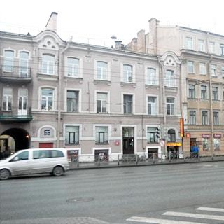 На фото: часть фасада оштукатуренного трехэтажного кирпичного дома, классический стиль, подвал с окнами, две парадные, арка во двор, балконы на втором и третьем этаже, прилегающий тротуар отделен от проезжей части ограждением