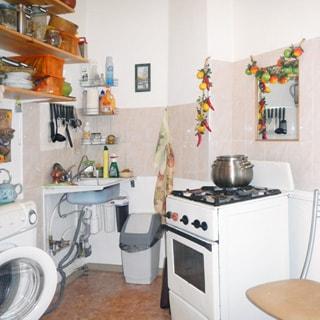На фото: часть помещения кухни, 4-комфорочная газовая плита с духовкой, раковина, стиральная машина, навесные кухонные полки, полы - линолеум, стены облицованы плиткой
