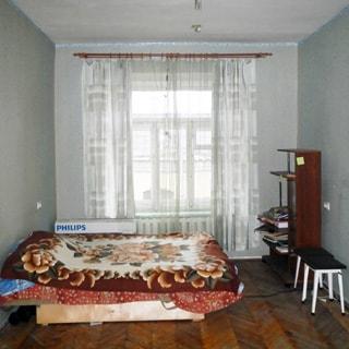 На фото: часть помещения жилой комнаты, одно трехстворчатое окно, слева у стены - диван-кровать, справа у стены - стеллаж и два табурета, полы - паркет