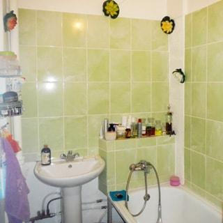 На фото: часть помещения ванной комнаты, керамическая раковина на стойке со смесителем, ванная со смесителем, стены облицованы салатовой керамической плиткой