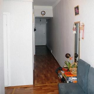 На фото: часть помещения прихожей и коридора, справа на стене большое зеркало, диван, полы - линолеум