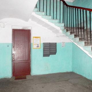 На фото: часть помещения лестничной клетки цокольного этажа, на стене - почтовые ящики, стены окрашены в голубой цвет, чисто, просторно