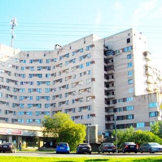 На фото: часть фасада многоэтажного кирпичного дома, одноэтажная пристройка, придомовая территория с газоном, кустарниками и деревьями, прилегающая проезжая часть асфальтирована, припаркованы автомобили