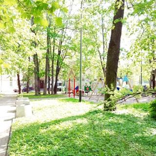 На летней фотографии: часть внутриквартальной придомовой территории, зеленые газоны, деревья, пешеходные дорожки, садовые скамейки, на заднем плане - детская площадка, за ней - жилой дом