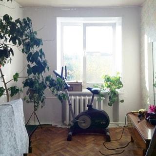 На фото: чистенькая комната, одно окно (стеклопакет), батарея центрального отопления, велотренажер, трильяж, полы - паркет.