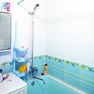 На фото: ванная комната, смеситель, стиральная машина, ванная голубого цвета, стены облицованы плиткой.