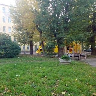 На фото: часть светлого благоустроенного зеленого двора с оборудованной детской площадкой, газоном, деревьями и кустами.