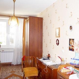 На фото: часть жилой комнаты, окно, установлен стеклопакет, под окном радиатор центрального отопления, справа у окна платяной шкаф, тумба, стул, стены оклеены обоями, на полу - ковер, на потолке - люстра