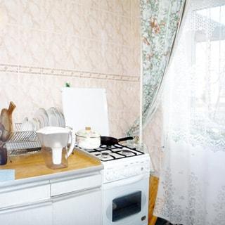 На фото: часть помещения кухни, справа - окно, слева вдоль стены газовая 4-комфорочная плита с духовым шкафом, кухонная тумба-стол, на столе - сушилка для посуды, стены - кафельная плитка