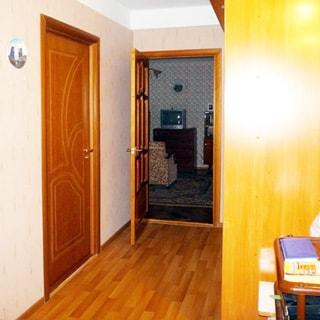 На фото: часть помещения прихожей, в центре на заднем плане открытая дверь в жилую комнату, справа у стены - шкаф-купе, слева - закрытая дверь, полы - линолеум
