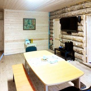 На фото: часть жилого помещения в доме - гостиной-столовой, посреди комнаты - большой обеденный стол, у стола - две скамьи и два стула, на правой стене закреплена телевизионная панель, под ней тумба, справа и слева от нее - двери в соседние помещения, прямо у дальней стены - журнальный столик, над ним - картина в раме, стены - бревенчатые, полы и потолок - дощатые
