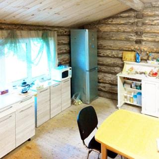 На фото: часть помещения кухни, большое окно, у окна - кухонные столы-тумбы, на столе - микроволновая печь, справа от окна в углу - двухкамерный холодильник, справа от него у стены - кухонный комод, на переднем плане обеденный стол, у стола - стул, стены - бревенчатые, полы и потолок - дощатые