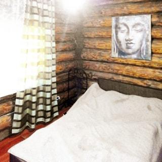 На фото: часть помещения спальни, одно окно, справа у стены - двуспальная заправленная кровать, над кроватью - эстамп, стены - бревенчатые, полы - ламинат