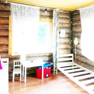 На фото: часть помещения детской комнаты, два окна, справа у окна - каркас детской кровати, слева у второго окна - детский стол со стулом и коробка с игрушками, стены бревенчатые, полы - ламинат, потолок - дощатый, на потолке - лампочка на проводе