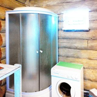 На фото: часть помещения санузла, в углу установлена душевая кабина, справа от нее у стены - стиральная машина с фронтальной загрузкой, над ней на стене - лампа дневного света, стены - бревенчатые