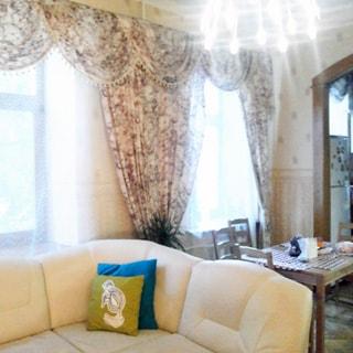 На фото: часть просторной светлой комнаты, два окна, мягкий диван, обеденный стол со стульями, на потолке - люстра