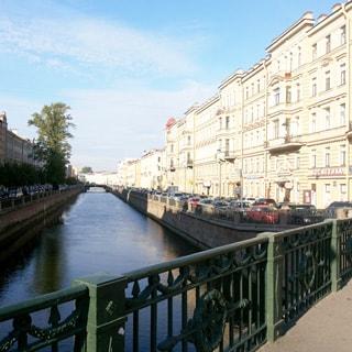 На фото: вид с моста на канал Грибоедова в сторону Вознесенского проспекта, справа на набережной - припаркованные автомобил, слева - высокие деревья