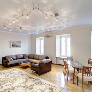 На фото: большая просторная светлая комната, три окна, на стене - кондиционер, полы - ламинат, ковер, мягкий диван и кресло, журнальный столик, обеденный стол со стеклянной столешницей, шесть стульев вокруг стола, на потолке композиция из светильников