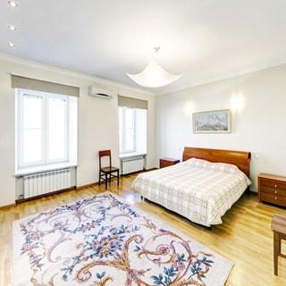 На фото: большая просторная светлая комната - спальня, два окна, на стене - кондиционер, полы - ламинат, ковер, двуспальная кровать, две прикроватные тумбочки, два стула, на потолке - люстра и точечные светильники