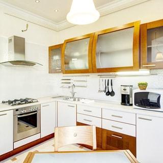 На фото: часть кухни (вид от окна), встроенная мебель светлых тонов, навесные шкафы, газовая плита с духовым шкафом и вытяжкой, металлическая мойка со смесителем, микроволновка и кофеварка, обеденный стол, стул, полы - плитка
