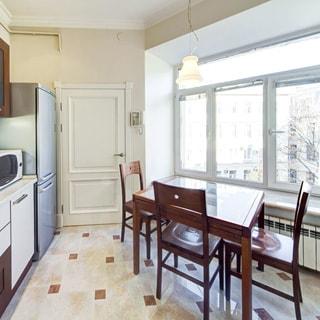 На фото: часть кухни (вид от плиты в сторону окна), большое трехстворчатое окно, слева - встроенная мебель, двухкамерный холодильник, входная дверь, домофон, у окна - обеденный стол со стульями, полы - плитка