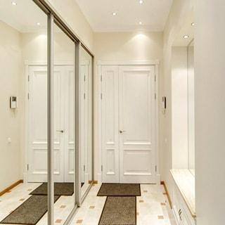 На фото: помещение прихожей, светлобежевые тона, слева - зеркальный шкаф-купе, справа - зеркало и тумба для обуви, в центре - входная дверь, домофон, полы - плитка, на потолке - точечные светильники