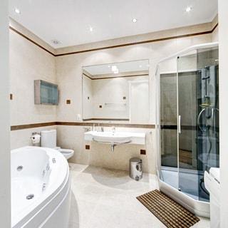 На фото: просторный санузел, слева - ванная-джакузи, за ней - унитаз-компакт, в центре - большая керамическая раковина со смесителем и большим зеркалом, справа - душевая кабина и стиральная машина, полы - плитка, на потолке - точечные светильники