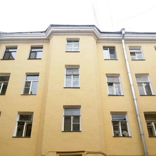 На фото: часть фасада оштукатуренного желтоватого кирпичного дома, классический стиль, новая водосточная труба, большинство окон - стеклопакеты