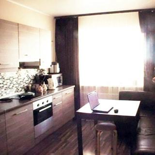 На фото: часть кухни, окно, справа от окна вдоль правой стены - мягкий диван и обеденный стол, слева вдоль стены - встроенная кухня: столы-тумбы, навесные шкафы, электрическая жарочная панель, духовой шкаф, кухонный фартук.