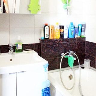 На фото: часть ванной комнаты, ванная со смесителем для ванной, керамическая раковина со смесителем, под раковиной - напольный шкаф, стены - плитка.