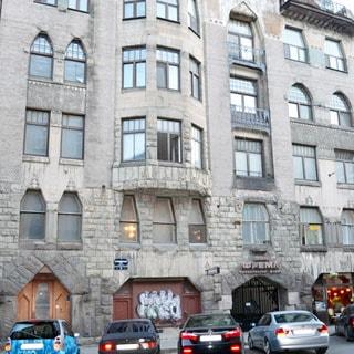 На фото: часть фасада пятиэтажного кирпичного дома, до третьего этажа фасад облицован декоративным камнем, без балконов, с третьего этажа - эркер, ворота во двор закрыты, в первом этаже - витринные окна, у тротуара припаркованы автомобили.