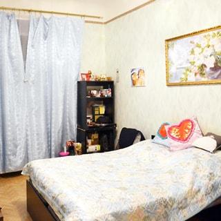 На фото: часть помещения жилой комнаты - спальни, окно закрыто шторами, справа от окна - небольшой стеллаж, справа у стены - двуспальная кровать, над ней на стене - эстамп, стены оклеены светлыми обоями, полы - паркет.