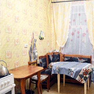 На фото: часть помещения кухни, окно, слева у окна - угловой диван и обеденный столик, левее - стул и еще один столик, еще левее - газовая плита с духовым шкафом, стены оклеены светлыми обоями, полы - линолеум.