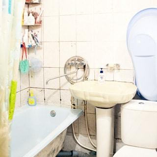 На фото: часть помещения санузла, в центре - керамическая раковина на стойке, слева - ванная, в углу над ванной - полочки для мыльных принадлежностей, смеситель - общий для раковины и ванной, справа - унитаз компакт, стены облицованы керамической плиткой.