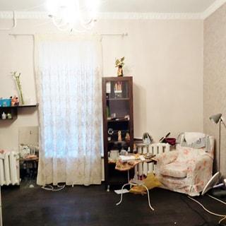 На фото: чистая светлая комната со свежим ремонтом, одно окно, две батареи центрального отопления: по одной справа и слева от окна, кресло, шкаф-пенал, журнальный столик, торшер.