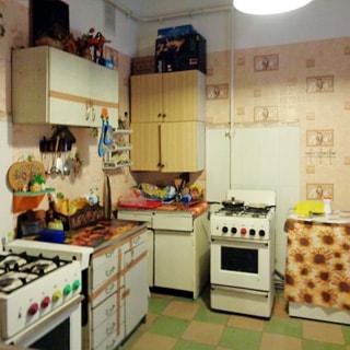 На фото: часть кухни, две газовые 4-комфорочные плиты, три стола-тумбы, навесные шкафы, кухонная посуда, полы - линолиум.
