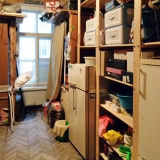 На фото: помещение кладовой, одно окно, справа и слева от окна - стеллажи и шкафы с вещами, два двухкамерных холодильника, полы - паркет.