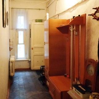 На фото: коридор-прихожая, одно окно, слева на стене - батарея центрального отопления, справа одежные шкафы и вешалки, входная дверь, полы - паркет.