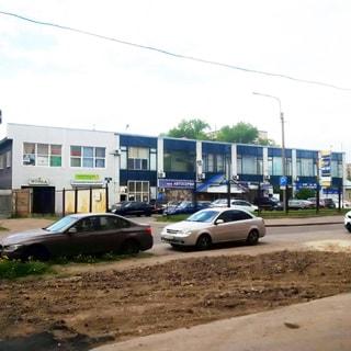 На фото: 2-этажное типовое здание бытового обслуживания с витринными окнами, вход в здание с крыльцом, придомовая территория - стоянка для автомобилей огорожена