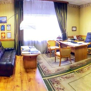 На фото: внутреннее помещение с окном и офисной мебелью - письменные столы, стулья, кресло, диван, на полу - ковер