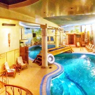 На фото: помещение СПА центра с бассейном, у бассейна - кресла для отдыха