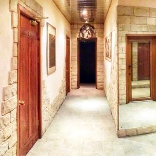 На фото: коридор, стены декорированы камнем, зеркалами, полы - плитка